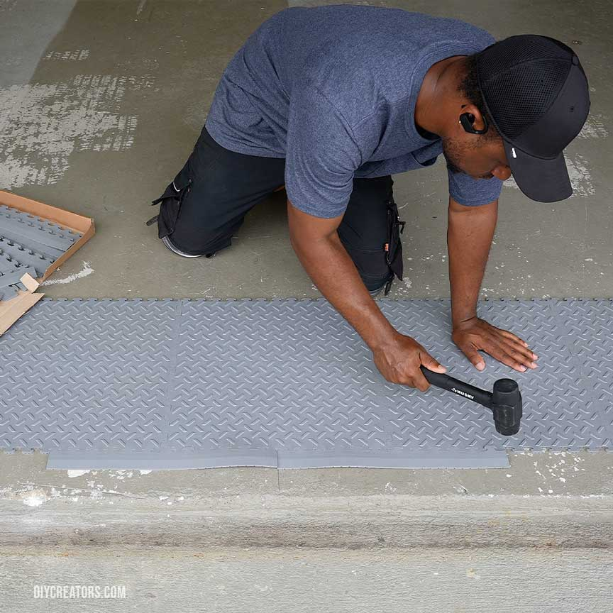 Use a rubber mallet to connect the Husky PVC flooring tiles