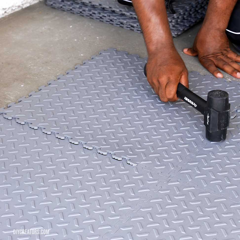 A close up of connecting Husky PVC flooring with a rubber mallet